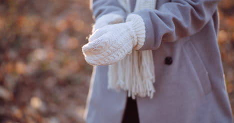 Woman-Putting-Wool-Gloves-On-Hands-In-Winter