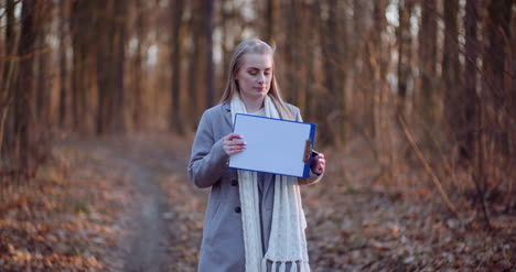 Woman-Holding-Blank-Paper-In-Front-Of-Camera