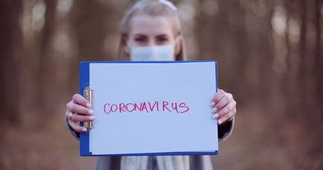 Woman-With-Protective-Mask-Holding-Coronavirus-Inscription-In-Hands-In-Forest