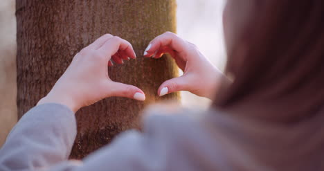Woman-Make-Heart-Shape-With-Hands-In-Forest-2