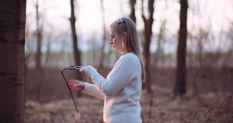 Woman-Uses-A-Stethoscope-And-Examines-A-Tree-In-The-Forest