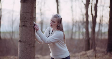 Woman-Uses-A-Stethoscope-And-Examines-A-Tree-In-The-Forest-2
