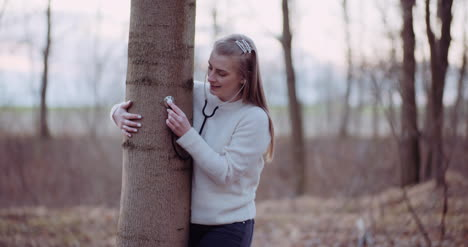 Woman-Uses-A-Stethoscope-And-Examines-A-Tree-In-The-Forest-4