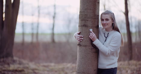 Woman-Uses-A-Stethoscope-And-Examines-A-Tree-In-The-Forest-5