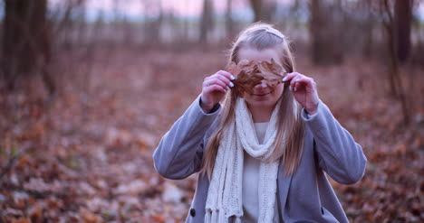 Smiling-Woman-Hiding-Eyes-With-Leaves-In-Autumn-1