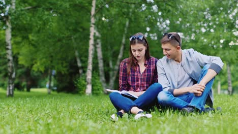 Young-Man-And-Woman-Sitting-On-Grass-Looking-at-Book
