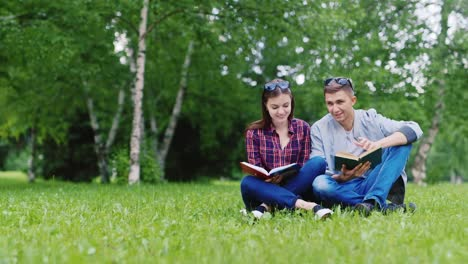 Young-Man-And-A-Woman-Reading-A-Book-In-The-Park-They-Sit-On-A-Green-Lawn-Hd-Video