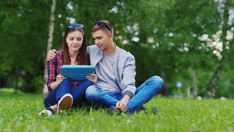 Young-Girl-And-A-Guy-Used-A-Tablet-In-The-Park-Boy-Embraces-Girl-Hd-Video