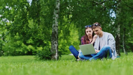 Friends-Of-Man-And-Woman-Sitting-On-The-Grass-In-The-Park-Enjoy-A-Laptop-Hd-Video
