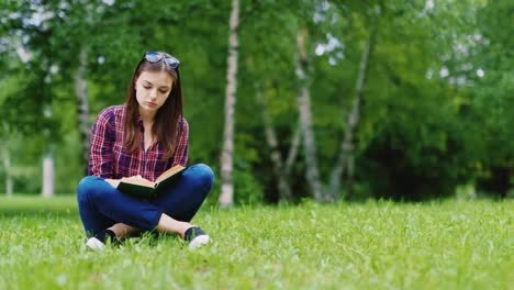 Attractive-Female-Student-Reading-A-Book-In-The-Park-Sitting-On-The-Lawn-Hd-Video