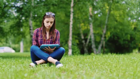 A-Female-Student-Is-Preparing-For-Exams-Sits-On-A-Lawn-In-The-Park-Enjoys-A-Tablet-Hd-Video