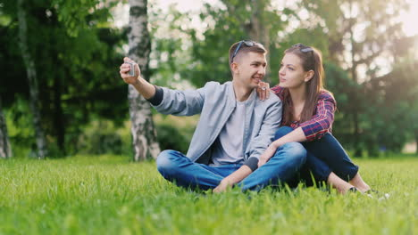 Young-Couple-Photographing-Themselves-On-The-Phone-Making-Funny-Faces-Sitting-In-The-Park-On-The-Gra