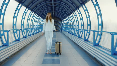 Young-Business-Woman-With-Travel-Bag-On-Wheels-Is-On-The-Transition-From-The-Terminal-At-The-Airport