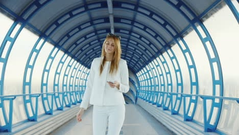 A-Stylish-Woman-Walks-Through-A-Glass-Tunnel-Listening-To-Music-On-Headphones