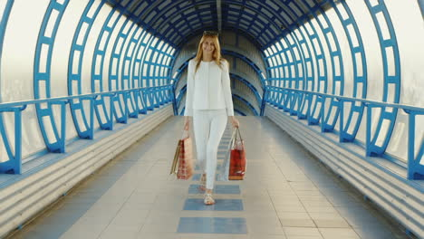 Steadicam-Shot-Stylish-Young-Woman-With-Shopping-Bags-Talking-On-Modern-Glass-Transition-Or-A-Tunnel