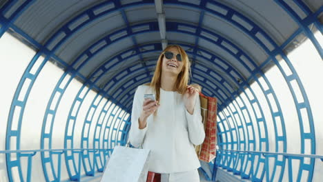 A-Stylish-Woman-Comes-With-Shopping-Bags-Talking-On-The-Phone-Successful-Shopping-Concept