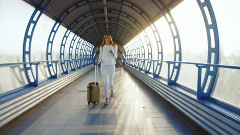Steadicam-Shot-Life-In-Motion-Stylish-Woman-With-Travel-Bag-Is-On-The-Sunlit-Move-Between-Terminals