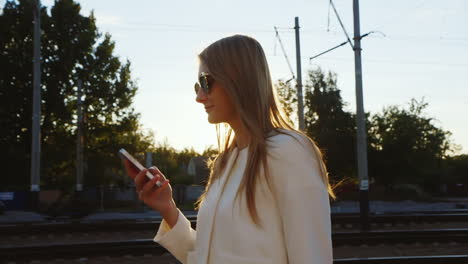 Attractive-Woman-Walking-Along-Train-Station-Platform-Uses-The-Phone-Steadicam-Shot