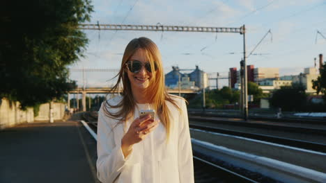 A-Business-Woman-Is-Walking-Along-The-Railway-Station-Using-A-Smartphone-Communication-In-The-Travel