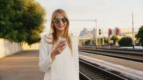 Portrait-Of-Successful-Business-Woman-On-A-Trip-He-Talks-On-The-Phone-At-The-Railway-Station