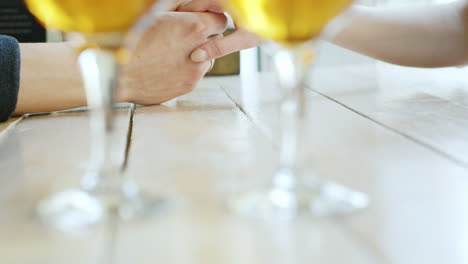 Hands-Of-A-Young-Couple-Two-Glasses-Of-Wine-In-The-Foreground