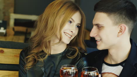 Man-And-Woman-20-25-Years-In-The-Cafe-Holding-Wine-Glasses-Flirting-Smiling