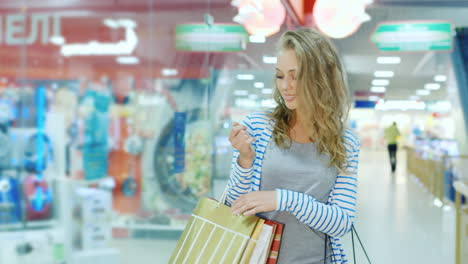 Happy-Young-Woman-With-Shopping-Bags-Goes-Along-Storefronts-Shopping-Center-Hd-Video