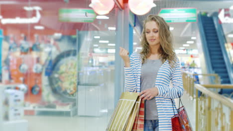 Attractive-Young-Woman-With-Many-Shopping-Bags-Goes-Along-Storefronts-Shopping-Center