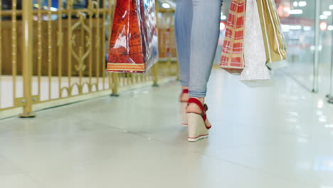 Young-Woman-In-Jeans-And-Red-Shoes-Walking-On-The-Mall-Rear-View-The-Frame-Can-Be-Seen-Only-The-Legs