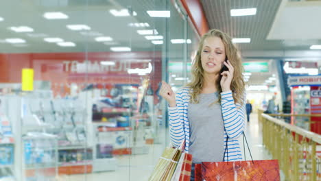 An-Attractive-Woman-With-Shopping-Bags-Walking-On-The-Mall-Talking-On-Mobile-Phone-Hd-Video