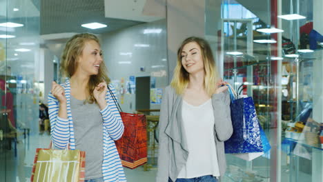 Two-Attractive-Women-Go-Through-The-Mall-With-Shopping-Bags-Talking-Hd-Video