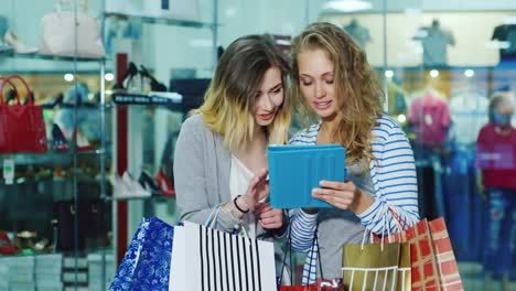 Two-Woman-Friends-With-Shopping-Bags-Used-By-The-Tablet-They-Stand-On-A-Background-Of-Glass-Windows-
