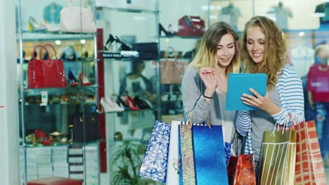 Two-Friends-In-The-Store-Use-The-Tablet-They-Stand-On-A-Background-Of-Glass-Windows-With-Goods-Hd-Vi