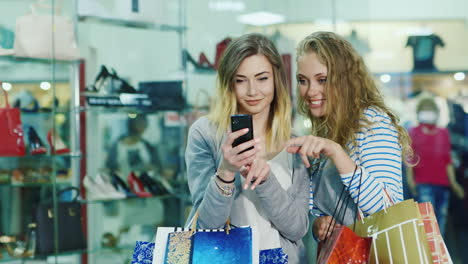 Two-Attractive-Woman-Looking-At-The-Photos-On-The-Phone-In-The-Hands-Have-A-Lot-Of-Shopping-Bags-Smi