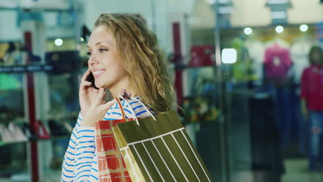 An-Attractive-Woman-With-Shopping-Bags-Talking-On-The-Phone-It-Is-Against-The-Background-Of-Glass-Sh