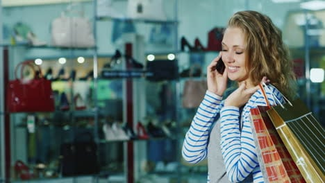 Young-Attractive-Woman-Talking-On-The-Phone-She-Has-A-Lot-Of-Shopping-Bags-It-Is-Opposite-The-Shop-W
