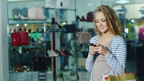 Attractive-Female-Shopper-With-Shopping-Bags-Uses-A-Smartphone-It-Is-Opposite-The-Glass-Showcases-Sh