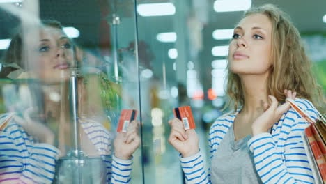 Attractive-Young-Woman-Looking-At-A-Glass-Display-Case-In-The-Store-The-Hands-Holding-The-Card-For-S