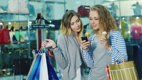Two-Young-Women-With-Shopping-Bags-Dyal-Go-Ice-Cream-And-Consider-Something-On-The-Phone-Smile-It-Is
