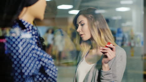 Attractive-Woman-Ready-For-Shopping-Examines-The-Shop-Window-Holding-A-Card-For-Purchases-She-Carrie