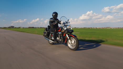 Travel-Dream---Biker-Rides-Along-A-Country-Road-On-A-Background-Of-Blue-Sky-And-Green-Fields