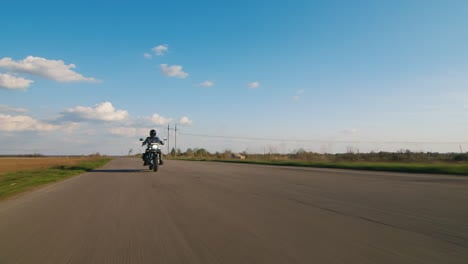 A-Lone-Biker-Riding-On-A-Deserted-Road-Wide-Angle