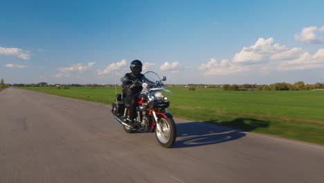Biker-Rides-On-The-Road-In-The-Countryside-Spring-Green-Fields-And-Blue-Sky