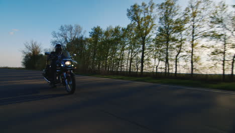 Biker-On-A-Motorcycle-Through-The-Trees-The-Sun-Shines