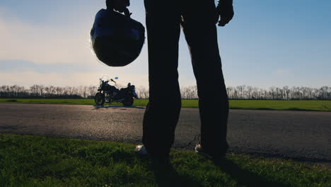 Biker-Holding-A-Helmet-On-A-Motorcycle-And-Looks-At-The-Sun