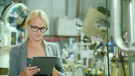 Woman-Uses-a-Tablet-by-a-Bottling-Production-Line