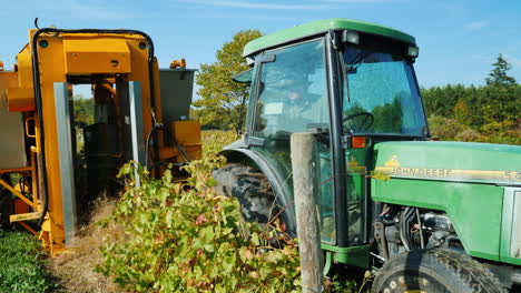 Farmer-Pulls-Mechanical-Grape-Harvester-With-Tractor