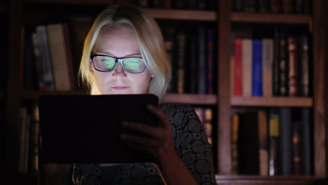 Woman-Works-on-Tablet-by-Bookshelf