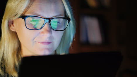 Woman-in-Glasses-Works-on-Tablet-at-Night
