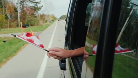 Hand-Holds-Canadian-Flag-Out-of-Car-Window